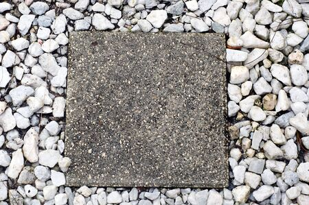 stepping: Square cement stepping stone surrounded by white marble chips on ground.