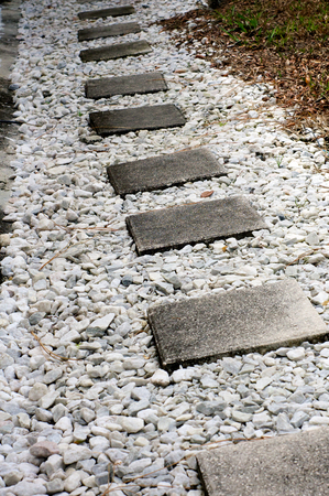 stepping on: Looking down a gravel path with cement square stepping stones surrounded by marble chips.