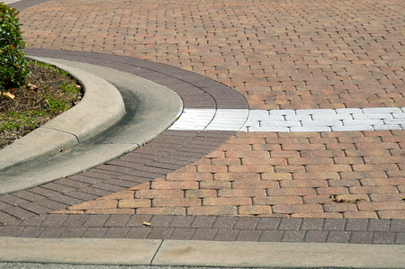 View of a curved red paver brick driveway with painted white line in bonita springs, florida.