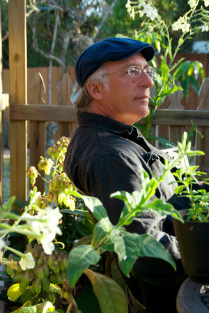 pleased: A mature man wearing a cap is sitting in his garden with a pleased look on his face surrounded by plants. Stock Photo