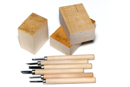 basswood: Six different wood carving tools and three blocks of basswood, over white, not isolated