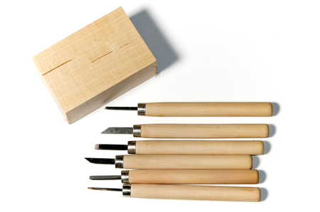Six different wood carving tools and a block of basswood, over white, not isolated Stock fotó
