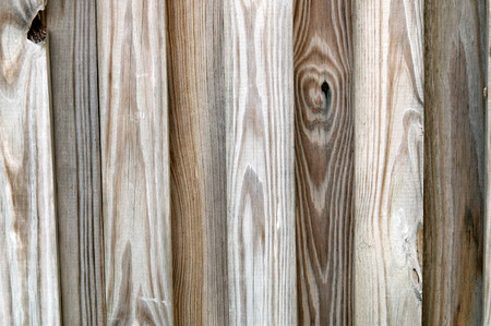 alternating: Detail of wooden, unfinished, privacy fence with slats alternating in depth.
