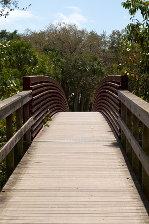 A wooden arched walking bridge with red metal side rails leads into forest in bonita springs, florida.