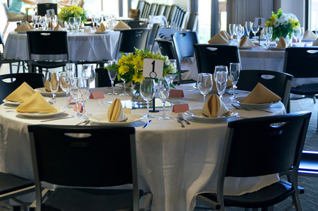 round chairs: Table number one at a clubhouse catered event, set with glasses, folded napkins and plates. Table is round with black plastic chairs. Stock Photo