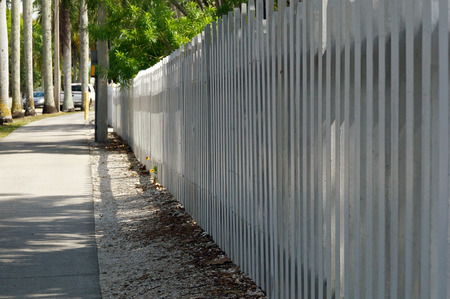 myers: A long white picket fence follows the sidewalk on McGregor Blvd in downtown Ft Myers Florida on a sunny morning.