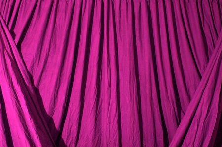 Close up of draped black theatrical curtain or backdrop, lit with pink gel.