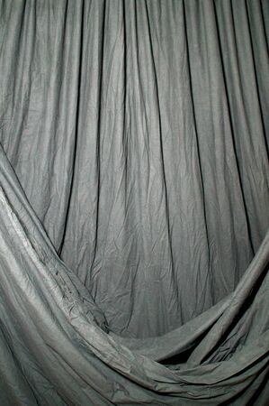 draped: Black draped theatrical curtain or backdrop lit by green gel. Stock Photo