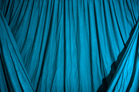 Close up of draped black theatrical curtain or backdrop, lit with blue gel. Banco de Imagens