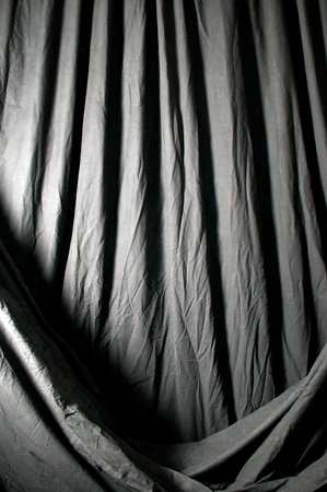 draped cloth: Vertical image of draped black theatrical curtain or backdrop. Stock Photo