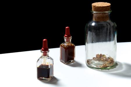 goteros: Dos botellas cuentagotas pequeñas con aceites esenciales de extractos herbarios y frasco grande con hierbas secas. Los aceites son pachulí y romero.