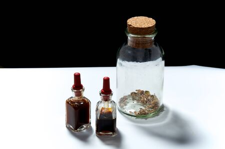 goteros: Two small eye dropper bottles with herbal extract essential oils and large jar with dried herbs. Oils are patchouli and rosemary. Foto de archivo