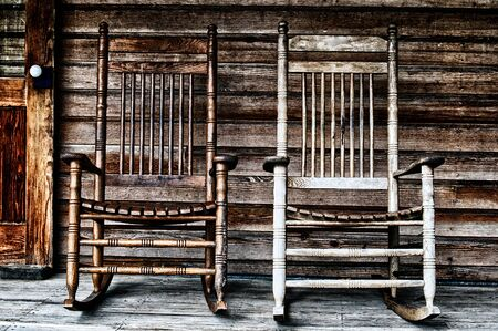 Two old wooden rocking chairs on front porch, part of door and the house's wooden shingles can be seen. Stock fotó
