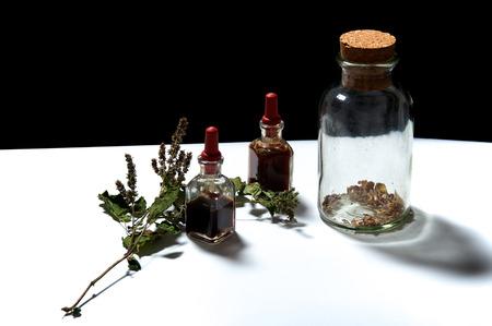 goteros: Dos botellas pequeñas de cuentagotas con aceites esenciales de extractos herbarios y frasco grande con hierbas secas y una ramita de pachuli .. Los aceites son pachulí y romero. Foto de archivo
