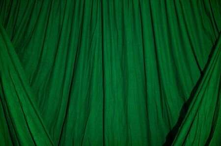 draped cloth: Close up of black draped theatrical curtain or backdrop lit with green gel or filter.