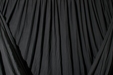 draped: Close up of black draped theatrical curtain or backdrop.