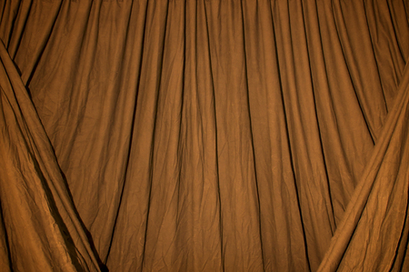 Close up of black draped theatrical curtain or backdrop lit with orange gel or filter.