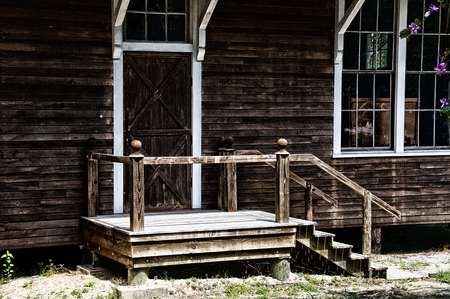 stoop: A closed wooden barn door at the top of a set of stairs on old weathered building.