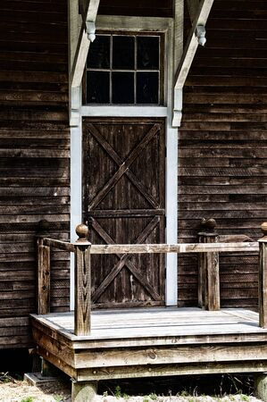 stoop: A wooden barn door at the top of a stoop on old weathered building.