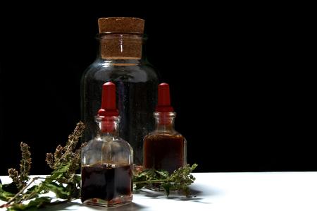 goteros: Dos botellas pequeñas de cuentagotas con aceites esenciales de extractos herbarios y frasco grande con hierbas secas y una ramita de pachuli .. Los aceites son pachulí y romero. Sobre la superficie blanca con fondo negro. Foto de archivo
