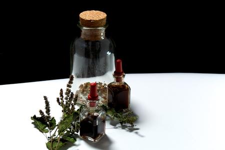 goteros: Dos botellas pequeñas de cuentagotas con aceites esenciales de extractos herbarios y frasco grande con hierbas secas y una ramita de pachuli .. Los aceites son pachulí y la superficie blanca rosemary.On con fondo negro.