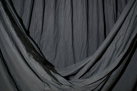 Close up of black draped theatrical curtain or backdrop lit with blue green gel or filter.