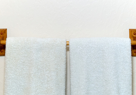 terrycloth: Two white cotton terry cloth towels hanging on an off white wall from wooden rack.