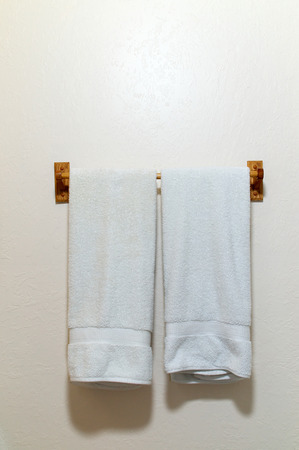 towels wall: Two white cotton terry cloth towels hanging on an off white wall from wooden rack,  with copy space Stock Photo