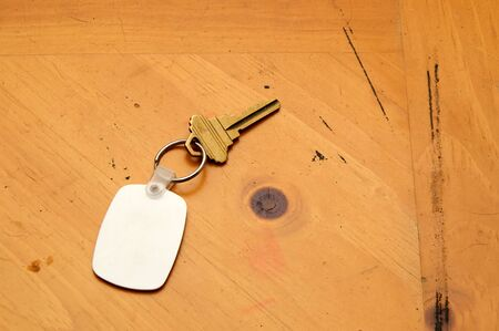 key fob: A blank white rubber key fob on keyring with a single brass key laying on old wooden table. Copy space on fob and wood.