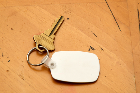 fob: A blank white rubber key fob on keyring with a single brass key laying on old wooden table. Copy space on fob and wood.