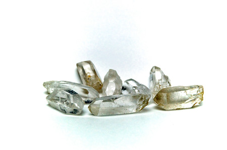 quartz crystal: A group of eight clear quartz crystal points on white surface, not isolated.