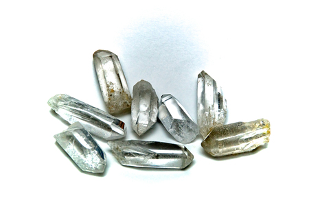 A group of eight clear quartz crystal points on white surface, not isolated.