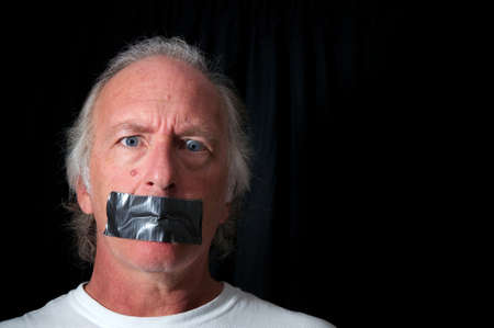 correctness: Studio portrait of an older blue eyed man with mouth duct taped closed, looking distraught, black background with copy space. Political correctness or freedom of speech concept.