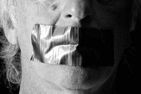 correctness: an older mans mouth is covered and taped closed with duct tape, side lit with half of face in shadow, finished in black and white. Stock Photo