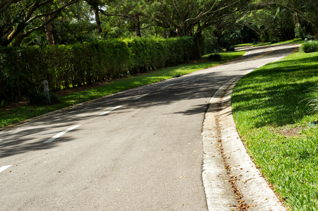 A beautifully landscaped road curves around the corner in Naples Florida, clean and well maintained lined with trees and hedges.