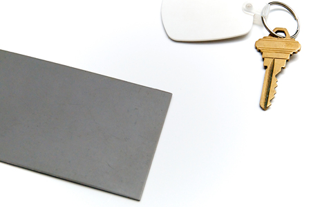 behind the scenes: A behind the scenes image of grey card positioned near key to be photographed. Grey card is a tool used for exposure and white balance in photography. Over white, not isolated.