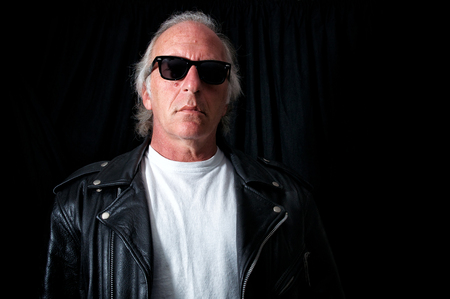 Imposing image of older biker against black backdrop looking down at viewer from behind vintage sunglasses. wearing vintage black leather jacket and white t shirt. Archivio Fotografico
