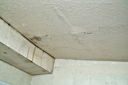 water damage: Looking up towards ceiling at water damage, stained and bubbled up paint from  leakage caused by rain. Stock Photo