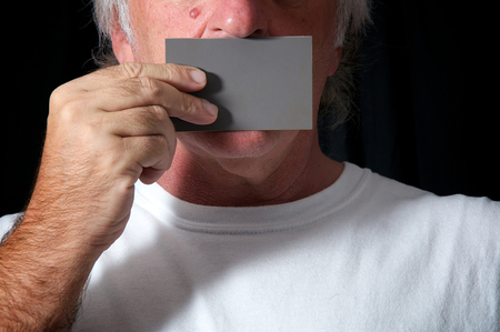 mouth close up: Close up of a man holding a grey card over his mouth against a black background wearing white t shirt. Censorship or freedom of speech concept.