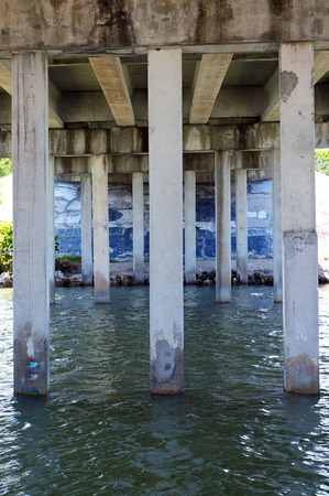 underneath: View from underneath concrete bridge of pylons and water moving south.
