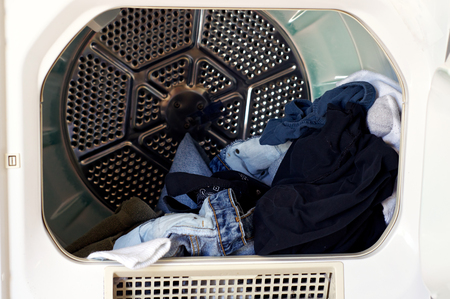appliance: Looking into a front loading clothes dryer with dried laundry.