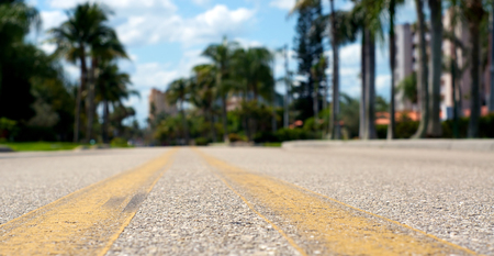 low angle views: Ground level view of road between yellow lines, shallow depth of field.