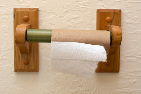 unlucky: Close up view of end of toilet paper roll showing cardboard roll on wooden holder and half a square of paper. Stock Photo