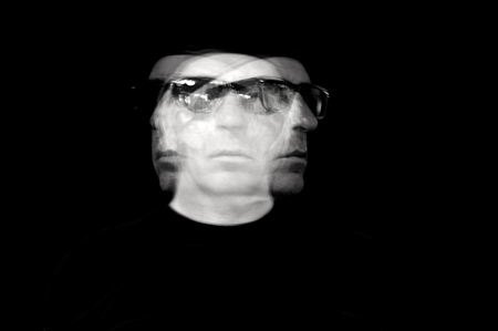 Long exposure image of a man looking in three directions trying to decide which way to go, in sunglasses against a black background.