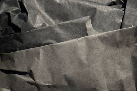 Close up of thick black semi gloss paper folds with strong shadows.