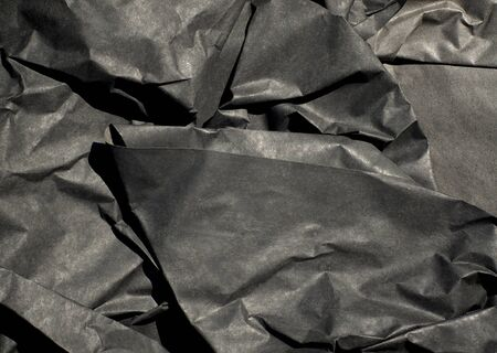 Close up of thick black semi gloss paper crumpled up with harsh shadows. Banco de Imagens