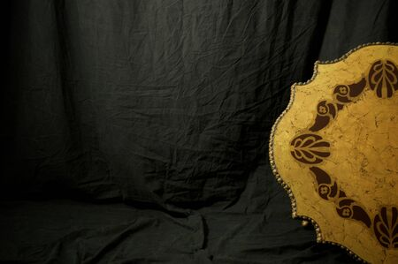 A black cloth backdrop fills the image with a portion of a large antique golden medallion seen on the right.