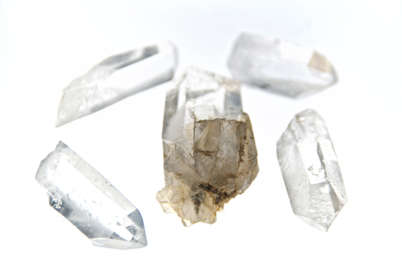 Five Clear Quartz Crystal Points Over White.  Not Isolated. Used for healing and energy work. Lit from beneath.