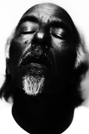 Dark high contrast black and white portrait of man looking dead, focus on nose and mouth. Shallow depth of field. Stock Photo
