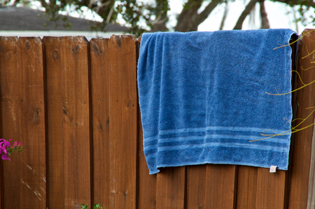 An old blue beach towel is hanging on a fence outside to dry.